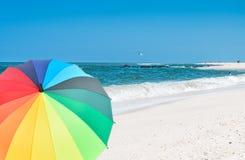 Χρωματισμένη ομπρέλα στην παραλία με την άσπρους άμμο και το μπλε ουρανό Στοκ εικόνα με δικαίωμα ελεύθερης χρήσης