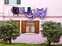 Χρωματισμένη πρόσοψη σε Burano με το πλυντήριο που κρεμά στον ήλιο Στοκ Εικόνες