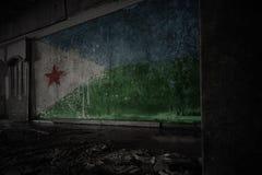Χρωματισμένη σημαία του Τζιμπουτί στο βρώμικο παλαιό τοίχο σε ένα εγκαταλειμμένο σπίτι στοκ φωτογραφία