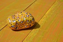 Χρωματισμένη τυπωμένη ύλη πέτρα λεοπαρδάλεων στο ξύλινο υπόβαθρο Στοκ εικόνα με δικαίωμα ελεύθερης χρήσης