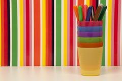 Χρωματισμένοι δείκτες, πλαστικά φλυτζάνια που συσσωρεύονται και πολύχρωμο υπόβαθρο λωρίδων Στοκ εικόνες με δικαίωμα ελεύθερης χρήσης