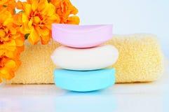 Χρωματισμένοι φραγμοί σαπουνιών, πετσέτα, λουλούδια Στοκ φωτογραφία με δικαίωμα ελεύθερης χρήσης