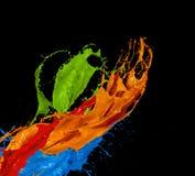 Χρωματισμένος παφλασμός χρωμάτων στο μαύρο υπόβαθρο Στοκ φωτογραφία με δικαίωμα ελεύθερης χρήσης