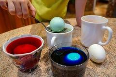 Χρωματισμένο αυγό για Πάσχα, διαδικασία, μπλε νερό στοκ εικόνες