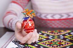 Χρωματισμένο αυγό Πάσχας με τα παραδοσιακά σχέδια στα θηλυκά χέρια Στοκ Εικόνα