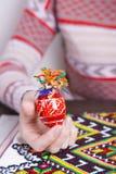 Χρωματισμένο αυγό Πάσχας με τα παραδοσιακά σχέδια στα θηλυκά χέρια Στοκ Εικόνες