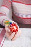 Χρωματισμένο αυγό Πάσχας με τα παραδοσιακά σχέδια στα θηλυκά χέρια Στοκ φωτογραφία με δικαίωμα ελεύθερης χρήσης