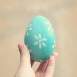 Χρωματισμένο αυγό Πάσχας χεριών εκμετάλλευση στοκ εικόνα
