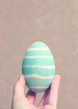 Χρωματισμένο αυγό Πάσχας χεριών εκμετάλλευση στοκ φωτογραφία με δικαίωμα ελεύθερης χρήσης