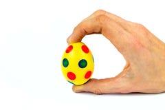 Χρωματισμένο κίτρινο αυγό Πάσχας χεριών εκμετάλλευση με τα σημεία Στοκ εικόνες με δικαίωμα ελεύθερης χρήσης