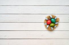 Χρωματισμένο φωλιά στεφάνι αυγών στο άσπρο ξύλινο υπόβαθρο σανίδων Στοκ Φωτογραφίες