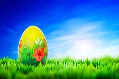 Χρωματισμένο χέρι αυγό Πάσχας στη χλόη διαθέσιμο μαύρο μπλε να αναπτύξει ανασκόπησης αφήνει στα λωρίδες κόκκινων ανοίξεων προτύπω Στοκ φωτογραφία με δικαίωμα ελεύθερης χρήσης