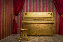 Χρωματισμένο χρυσός πιάνο με την καρέκλα Στοκ εικόνες με δικαίωμα ελεύθερης χρήσης