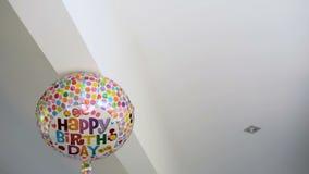 Χρόνια πολλά το ζωηρόχρωμο μπαλόνι κομμάτων εορτασμού είναι κολλημένο στο ανώτατο όριο απόθεμα βίντεο