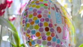 Χρόνια πολλά το μπαλόνι έφυγε μετά από το κόμμα με τα λουλούδια στο υπόβαθρο απόθεμα βίντεο