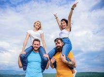 Χρόνοι διασκέδασης Ευτυχή άτομα piggybacking οι φίλες τους Αγαπώντας ζεύγη που αναπτύσσουν τις δραστηριότητες διασκέδασης υπαίθρι στοκ εικόνα με δικαίωμα ελεύθερης χρήσης