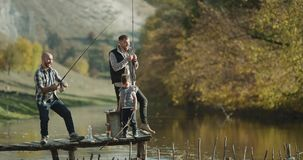 Χρόνος αλιείας για δύο φίλους και ένα μικρό αγόρι την ηλιόλουστη ημέρα που πιάνει τα ψάρια με την αλιεία της ράβδου 4K απόθεμα βίντεο
