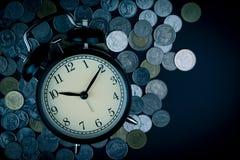 Χρόνος αποταμίευσης, ξυπνητήρι με τα νομίσματα που απομονώνονται στο μαύρο υπόβαθρο στοκ εικόνες