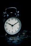 Χρόνος αποταμίευσης, ξυπνητήρι που στέκεται με τα νομίσματα που απομονώνονται στο μαύρο υπόβαθρο Με το εκλεκτής ποιότητας φίλτρο Στοκ Φωτογραφίες