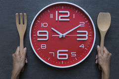 Χρόνος γεύματος με το ξυπνητήρι, το κουτάλι εκμετάλλευσης χεριών και το δίκρανο Στοκ Εικόνες