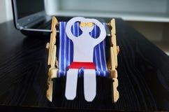 Χρόνος για τις διακοπές, άτομο εγγράφου σε μια καρέκλα ήλιων Στοκ Φωτογραφίες