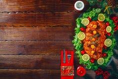 Χρόνος επιτραπέζιων γευμάτων Χριστουγέννων με τα ψημένα κρέατα που διακοσμούνται στο ύφος Χριστουγέννων Στοκ Εικόνα