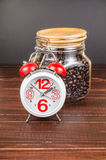 Χρόνος καφέ, ξυπνητήρι με το άσπρο φλυτζάνι καφέ και φασόλι καφέ μέσα Στοκ εικόνα με δικαίωμα ελεύθερης χρήσης