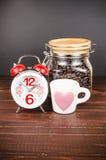 Χρόνος καφέ, ξυπνητήρι με το άσπρο φλυτζάνι καφέ και φασόλι καφέ μέσα Στοκ Εικόνα