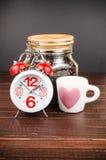 Χρόνος καφέ, ξυπνητήρι με το άσπρο φλυτζάνι καφέ και φασόλι καφέ Στοκ Εικόνες