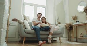Χρόνος κινηματογράφων για ένα νέο ζεύγος στις πυτζάμες που περνά μια ημέρα μαζί στον καναπέ είναι πολύ ευτυχείς τρώγοντας popcorn απόθεμα βίντεο