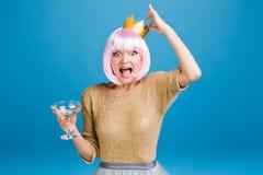 Χρόνος κομμάτων Brightful της αστείας νέας γυναίκας με τη σαμπάνια, χρυσή κορώνα στο κεφάλι που έχει τη διασκέδαση στο μπλε υπόβα στοκ εικόνες