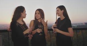 Χρόνος κόμματος στις κυρίες μπαλκονιών σοφιτών που πίνουν το κρασί και που κουβεντιάζουν, στο ηλιοβασίλεμα με το όμορφο υπόβαθρο  φιλμ μικρού μήκους