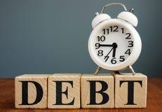 Χρόνος να πληρωθεί το χρέος Ξυπνητήρι και κύβοι στοκ εικόνα