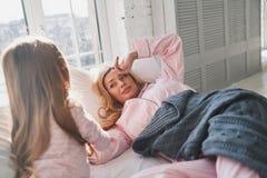 Χρόνος ξυπνήστε! Χαριτωμένο μικρό κορίτσι που ξυπνά την όμορφη μητέρα της Στοκ Εικόνες