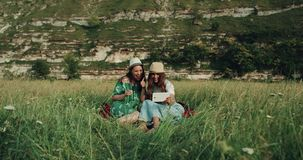 Χρόνος πικ-νίκ με δύο όμορφα κορίτσια, που καθορίζουν στο κάλυμμα και που κρατούν την ταμπλέτα μιλώντας με κάποιο απόθεμα βίντεο