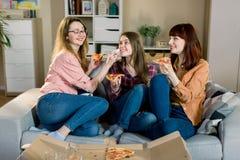Χρόνος πιτσών Τρεις όμορφες χαμογελώντας γυναίκες που τρώνε την πίτσα, που έχει τη διασκέδαση μαζί στην εγχώρια τραπεζαρία Friens στοκ φωτογραφίες με δικαίωμα ελεύθερης χρήσης