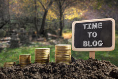 Χρόνος στην έννοια Blog Χρυσά νομίσματα στον εδαφολογικό πίνακα κιμωλίας στο θολωμένο φυσικό υπόβαθρο Στοκ φωτογραφία με δικαίωμα ελεύθερης χρήσης