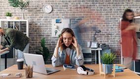 Χρόνος-σφάλμα ζουμ έξω της κουρασμένης νέας γυναίκας σχετικά με το κεφάλι στο γραφείο που αισθάνεται άρρωστης απόθεμα βίντεο
