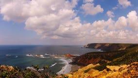 Χρόνος-σφάλμα που πυροβολείται μιας παραλίας με τους βράχους, την άμμο και τα γρήγορα κινούμενα κύματα και τα σύννεφα απόθεμα βίντεο