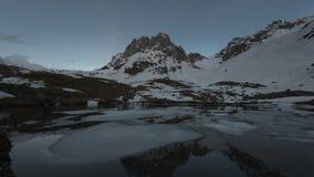 Χρόνος-σφάλμα του ηλιοβασιλέματος στα χιονώδη βουνά υπάρχει μια λίμνη με τους επιπλέοντες πάγους πάγου απόθεμα βίντεο