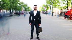 Χρόνος-σφάλμα του όμορφου τύπου που στέκεται στην οδό στο κέντρο της πόλης και που εξετάζει τη κάμερα φιλμ μικρού μήκους