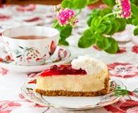 Χρόνος τσαγιού. Cheesecake φραουλών και φλυτζάνι του τσαγιού. Στοκ Εικόνες