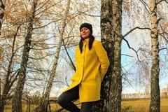 Χρόνος φθινοπώρου: όμορφο κορίτσι σε μια κίτρινη τοποθέτηση παλτών ενάντια σε ένα φθινοπωρινό δάσος σημύδων Στοκ φωτογραφίες με δικαίωμα ελεύθερης χρήσης