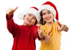 Χρόνος Χριστουγέννων - κορίτσι και αγόρι με το καπέλο Άγιου Βασίλη που παρουσιάζει ΕΝΤΑΞΕΙ σημάδι Στοκ Εικόνα