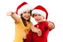 Χρόνος Χριστουγέννων - κορίτσι και αγόρι με το καπέλο Άγιου Βασίλη που παρουσιάζει ΕΝΤΑΞΕΙ σημάδι Στοκ φωτογραφίες με δικαίωμα ελεύθερης χρήσης