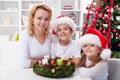 Χρόνος Χριστουγέννων - οικογένεια με το στεφάνι εμφάνισης στοκ εικόνα