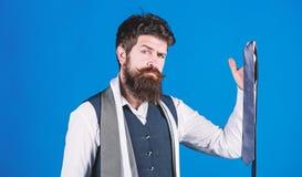 Χρώματα αντιστοιχιών Το γενειοφόρο hipster ατόμων κρατά λίγες γραβάτες στο μπλε υπόβαθρο Τύπος με τη γενειάδα που επιλέγει τη γρα στοκ εικόνες