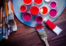 Χρώματα, βούρτσες και παλέτα στο ξύλινο υπόβαθρο Στοκ Φωτογραφίες