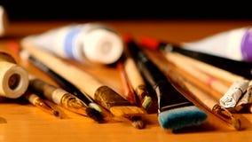 Χρώματα και βούρτσες, σωλήνες του χρώματος στον ξύλινο πίνακα φιλμ μικρού μήκους