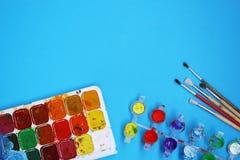 Χρώματα και βούρτσες Watercolor στο μπλε υπόβαθρο Στοκ Φωτογραφία